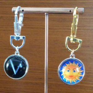 Two keyrings with glass globes showing sun and symbol for water