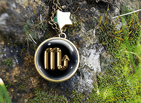 Metallic gold Scorpio glyph pendant with gold star bead on background of rock and moss